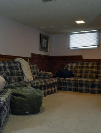 """My basement is definitely """"country"""". Think plaid and dark wood paneling, and that pretty much describes this space. You know what style I am not? Country! But, let's look at pictures of the basement anyways, along with my lovely little comments of issues I would change..."""